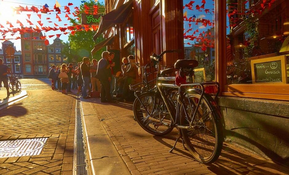 Vue d'une rue d'Amsterdam avec un vélo garé devant un café.