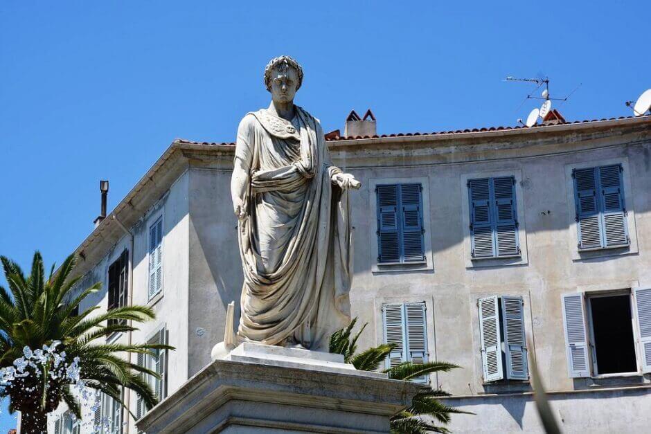 Napoléon représenté en empereur avec sa toge, sur une place ensoleillée de sa ville natale Ajaccio