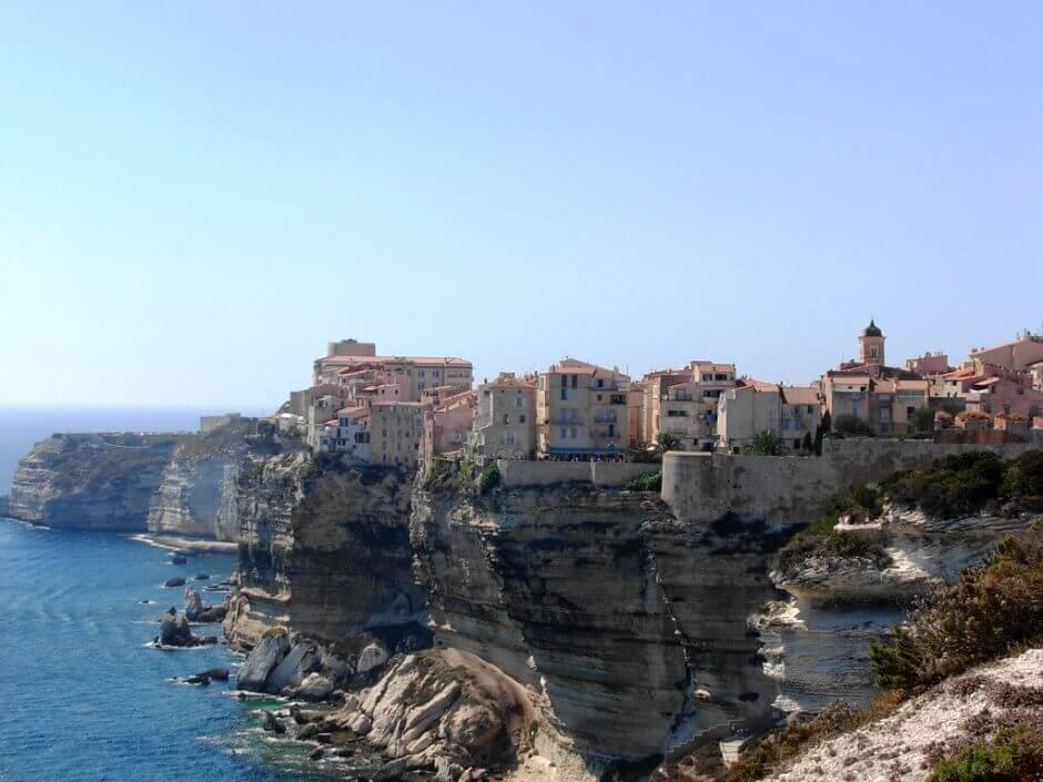 Maisons colorées de Bonifacio posées sur une falaise au-dessus de la Méditerranée.