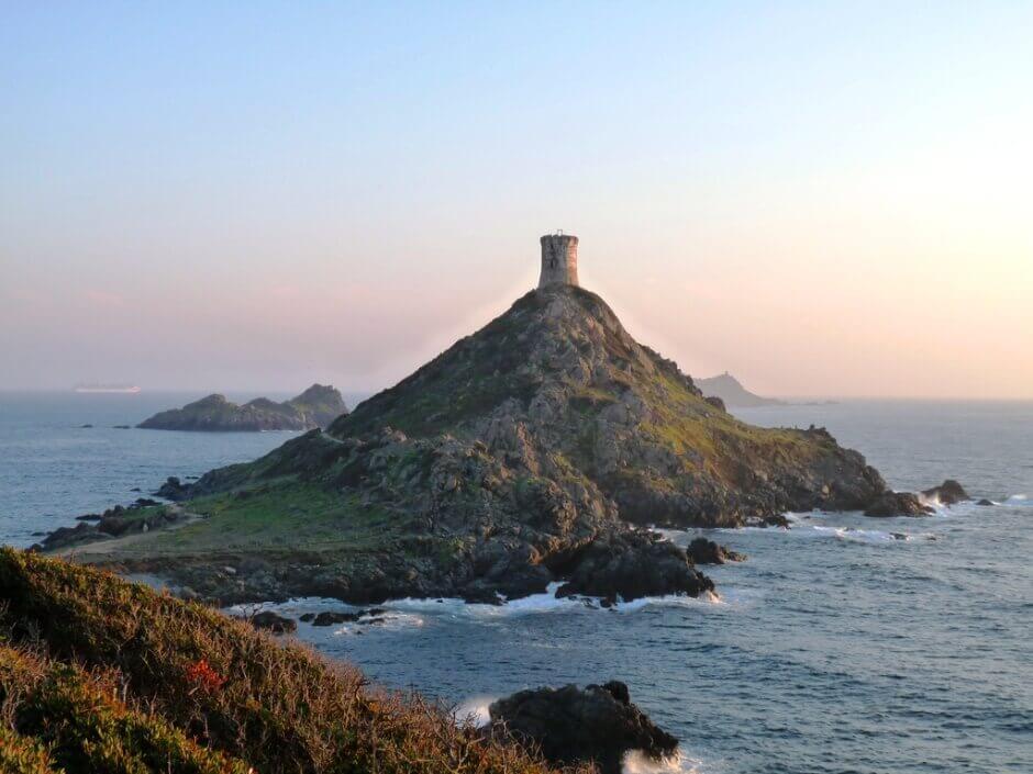 Vue d'un îlot couronné d'une tour au soleil couchant, en Corse.