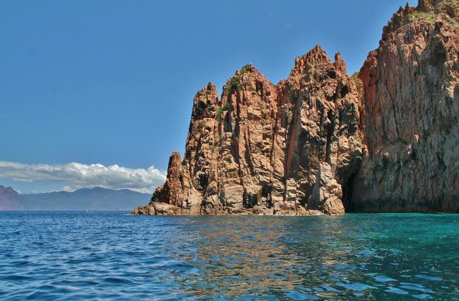 Vue d'une falaise rose plongeant dans la mer en Corse.