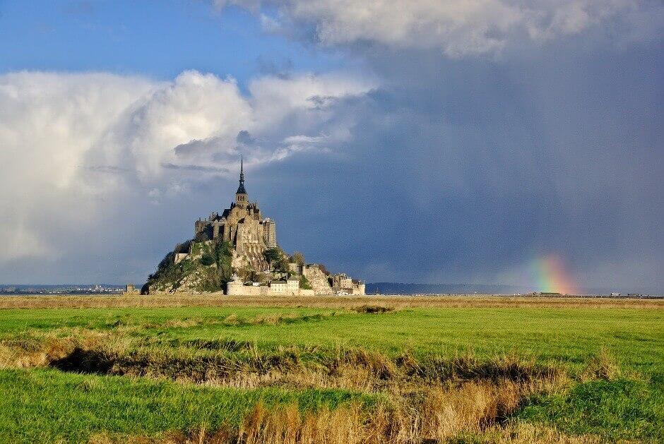 Vue du Mont-Saint-Michel avec un arc-en-ciel en arrière-plan.