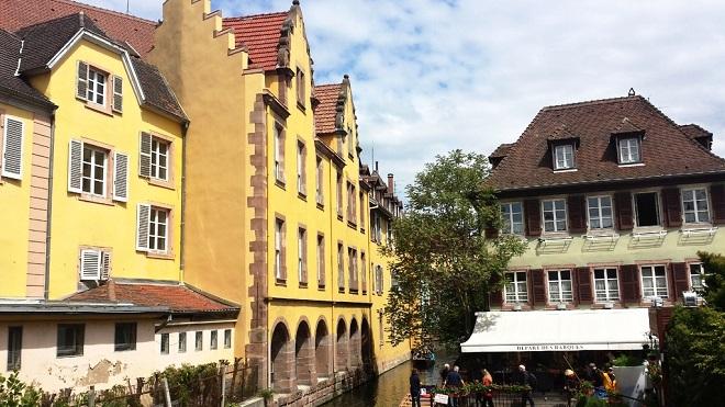 Vue sur une place avec une grande maison jaune à Colmar en Alsace.