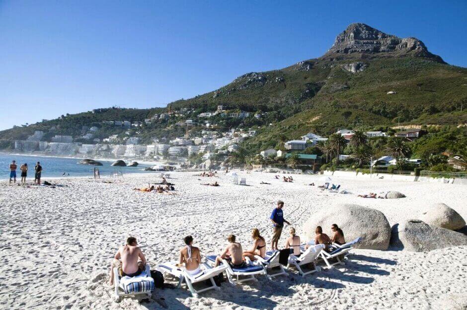 Vue d'une plage avec des personnes assises sur des chaises longues en Afrique du Sud.