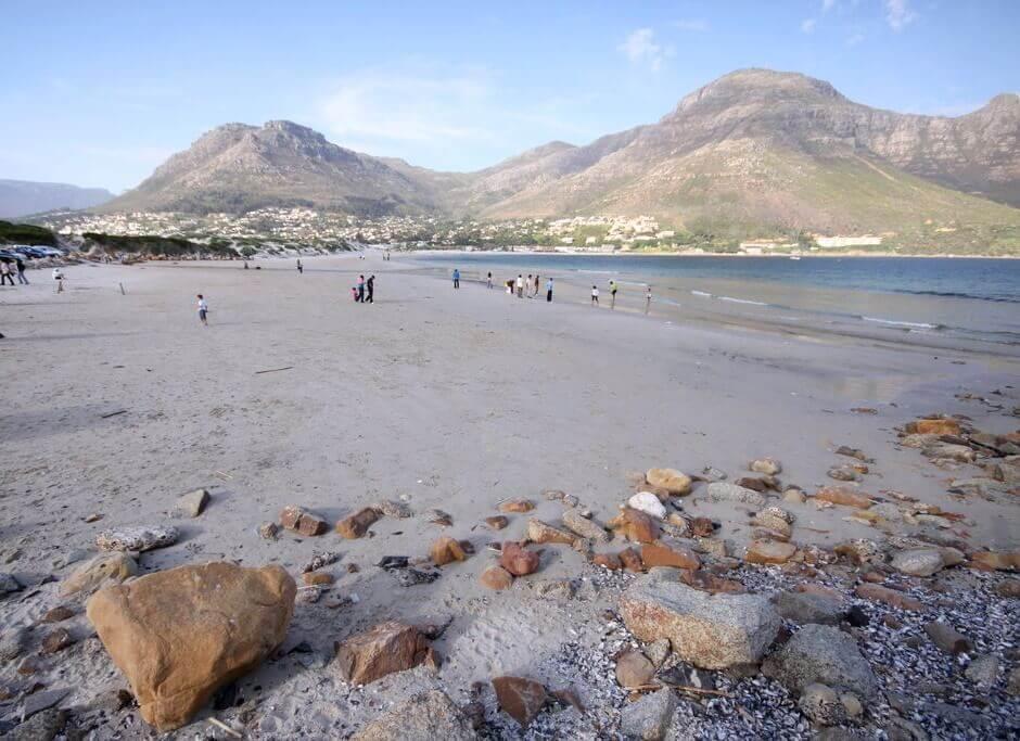 Vue d'une plage de sable et de cailloux, avec des montagnes en arrière-plan.