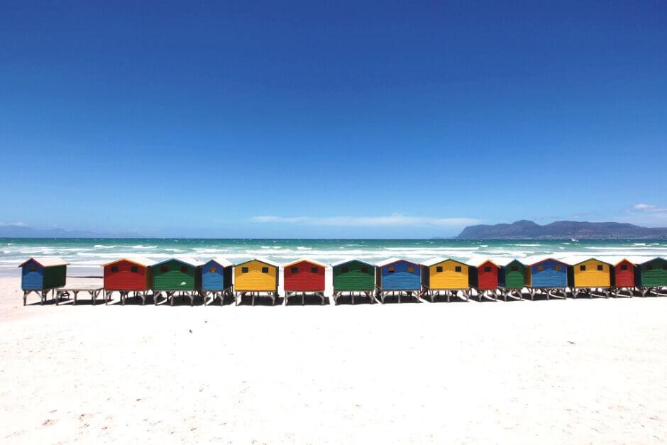 Vue de maisonnettes colorées alignées sur une plage de sable fin en Afrique du Sud.