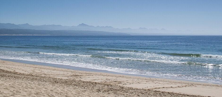Vue d'une plage avec des montagnes dans le lointain en Afrique du Sud.