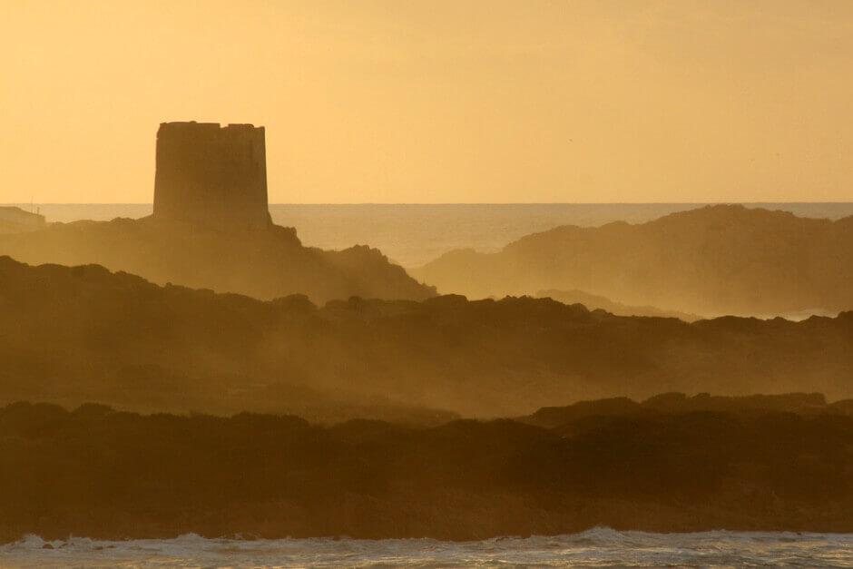 Vue d'une tour près de la mer au soleil couchant, en Sardaigne.