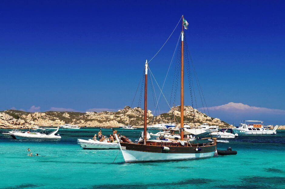 Des bateaux amarrés dans un mer transparente en Sardaigne.