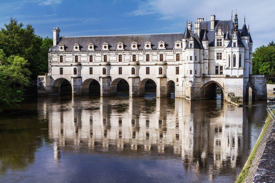 Vue d'un château construit comme un pont au-dessus d'une rivière.