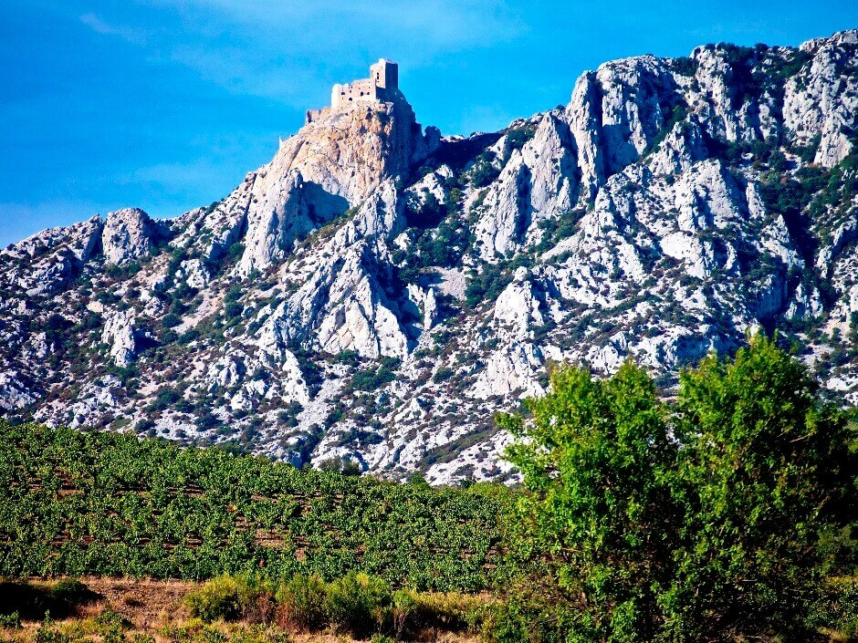 Vue d'une forteresse médiévale au sommet d'un piton rocheux.