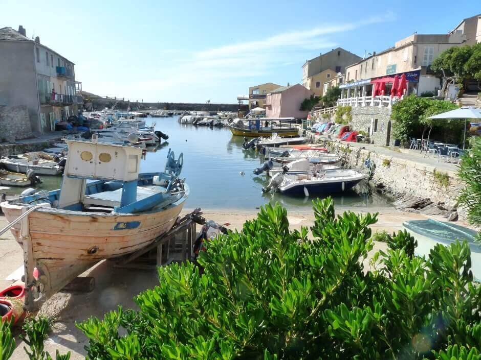 Vue d'un petit port avec des barques dans un village corse.