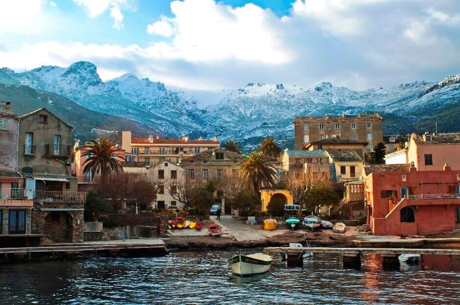 Vue d'un village corse au bord de la mer avec des montagnes enneigées en arrière-plan.