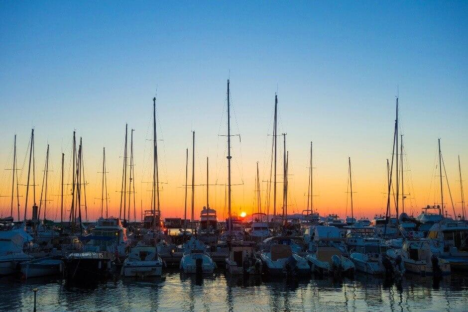 Vue d'un lever de soleil à travers les mâts de bateaux en Corse.