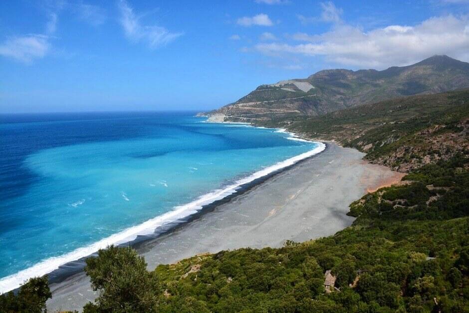 Vue plongeante sur une grande plage grise au pied d'une montagne en Corse.