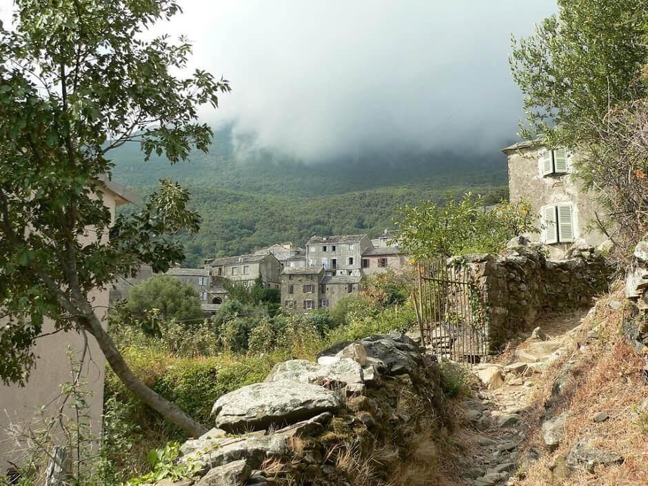 Vue d'un vieux hameau corse dans la montagne, traversé par un sentier.