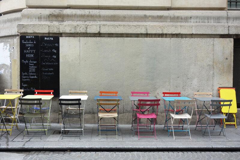 Tables et chaises colorées d'un café à Paris.