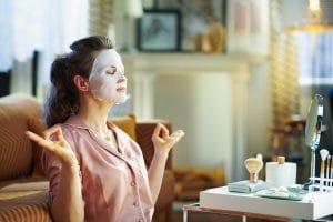 femme se relaxant avec un masque de beauté