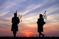 Hommes jouant de la cornemuse sous un coucher de soleil